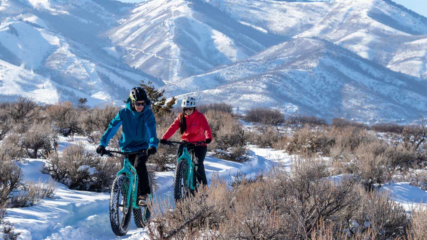 Two people fat biking on a trail above Park City, UT