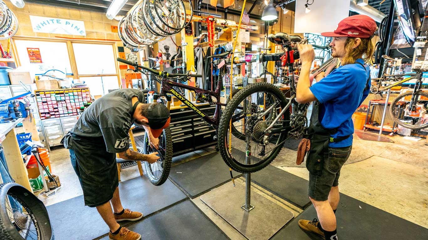 Two mechanics work on bikes in the White Pine Touring Bike Shop.