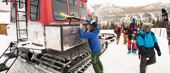 Skiers in front of a snow cat in the Uinta Mountains