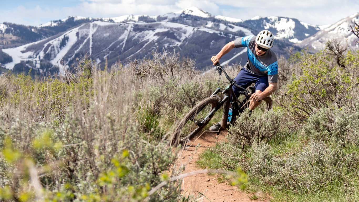 A mountain biker rounds a corner on a trail in Round Valley, Park City, UT.