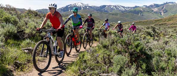 A group of women riding mountain bikes in Round Valley, Park City, UT.